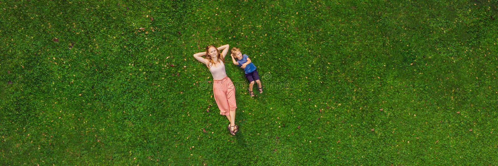 Mom and son are lying on the grass in the park, photos from the drone, quadracopter BANNER long format. Mom and son are lying on the grass in the park, photos royalty free stock images