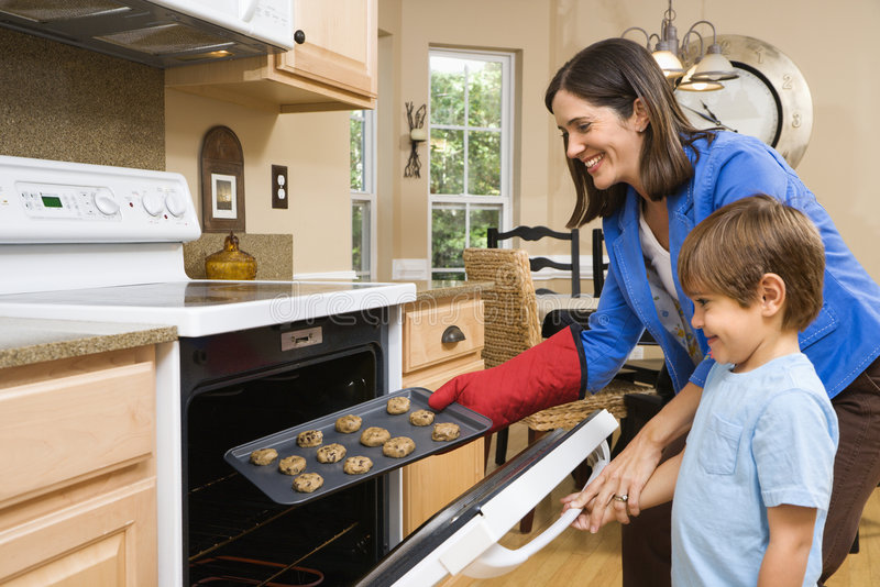Mom and son making cookies. stock images