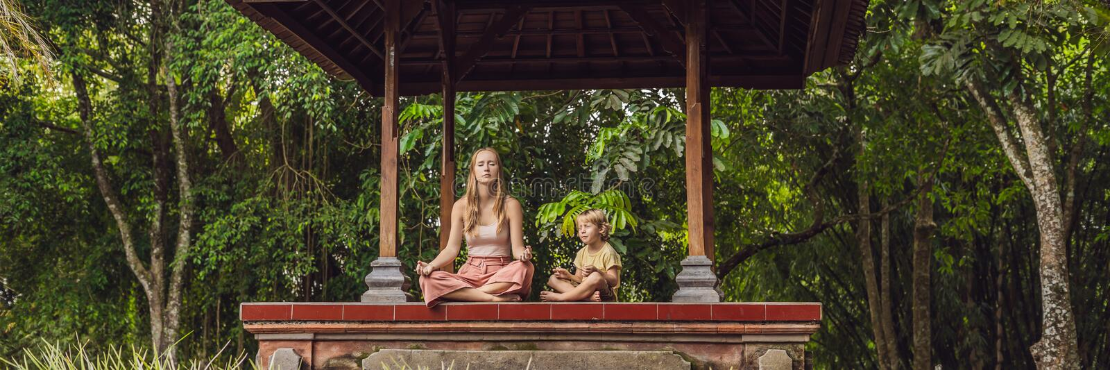 Mom and son meditate practicing yoga in the traditional balinesse gazebo BANNER, long format. Mom and son meditate practicing yoga in the traditional balinesse royalty free stock photos