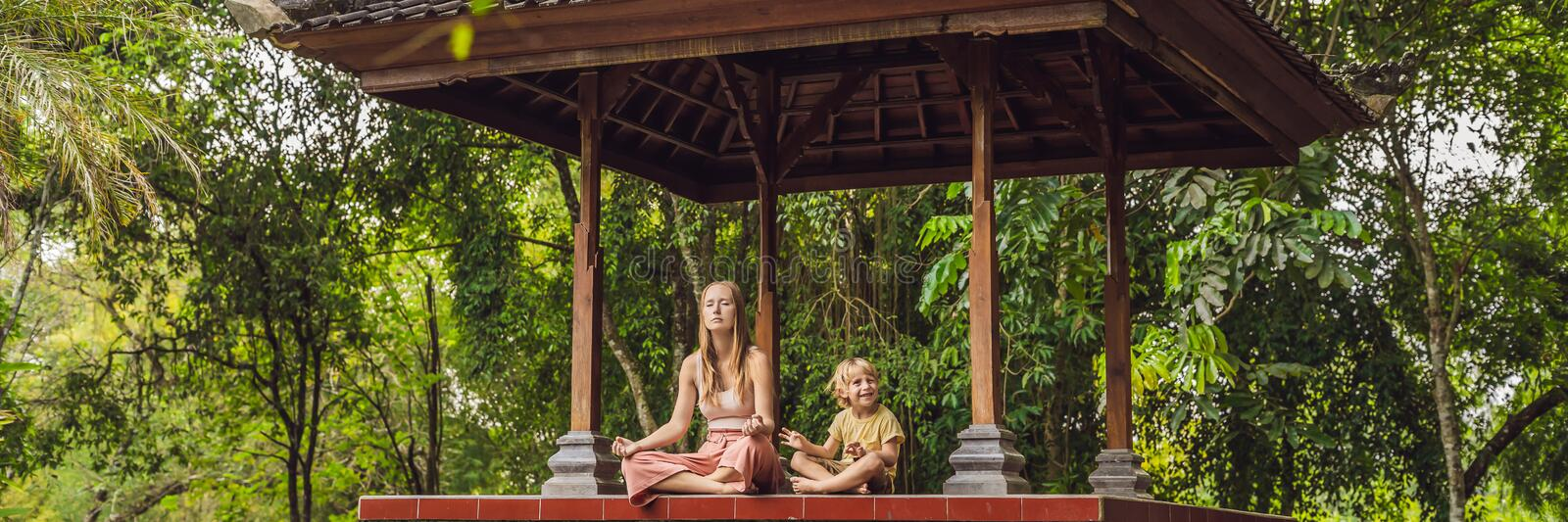Mom and son meditate practicing yoga in the traditional balinesse gazebo BANNER, long format. Mom and son meditate practicing yoga in the traditional balinesse royalty free stock photo