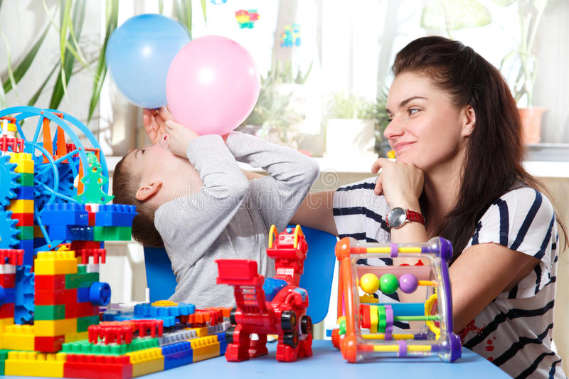 Mom and son playing with balloons stock image