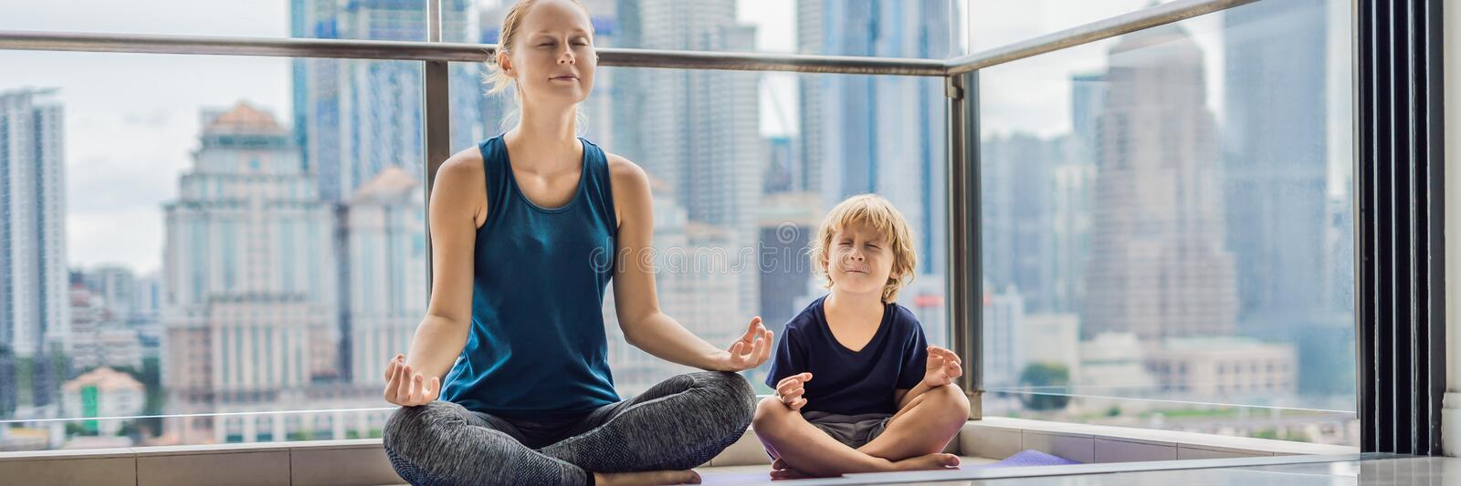 Mom and son are practicing yoga on the balcony in the background of a big city. Sports mom with kid doing morning work-out at home. Mum and child do the royalty free stock photos