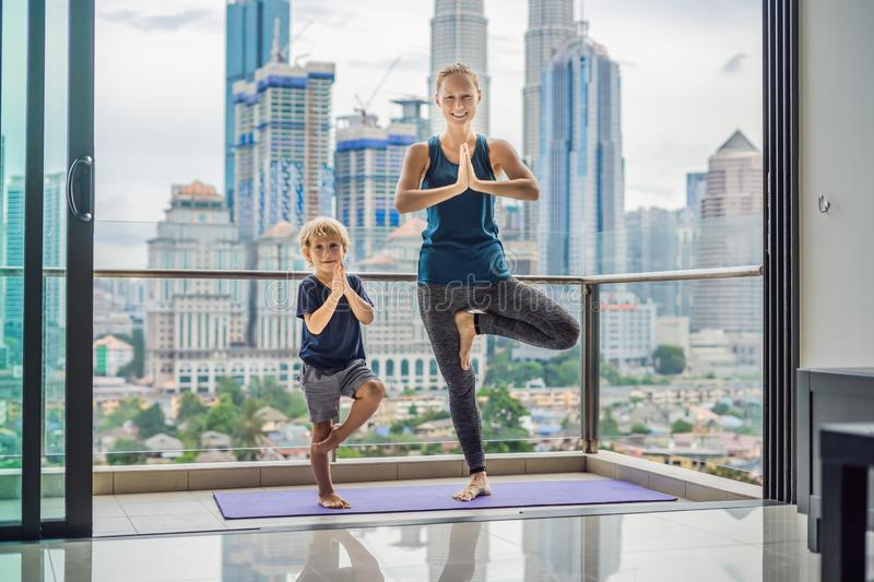 Mom and son are practicing yoga on the balcony in the background of a big city. Sports mom with kid doing morning work. Out at home. Mum and child do the royalty free stock images