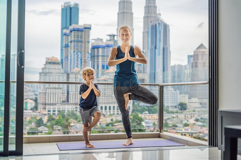 Mom and son are practicing yoga on the balcony in the background of a big city. Sports mom with kid doing morning work. Out at home. Mum and child do the royalty free stock photography