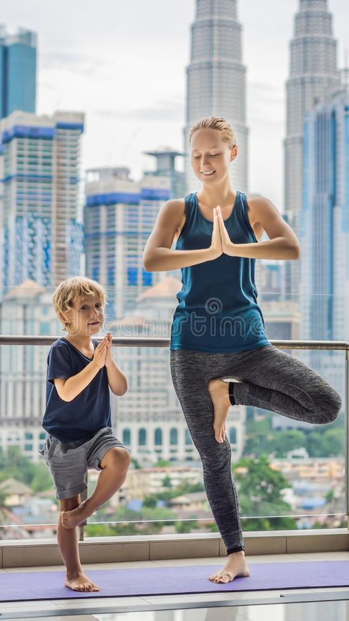 Mom and son are practicing yoga on the balcony in the background of a big city. Sports mom with kid doing morning work. Out at home. Mum and child do the stock images