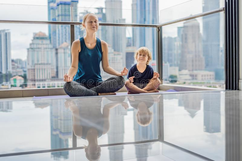 Mom and son are practicing yoga on the balcony in the background of a big city. Sports mom with kid doing morning work. Out at home. Mum and child do the stock image