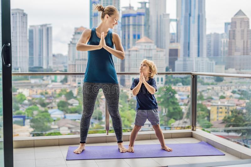 Mom and son are practicing yoga on the balcony in the background of a big city. Sports mom with kid doing morning work. Out at home. Mum and child do the royalty free stock image