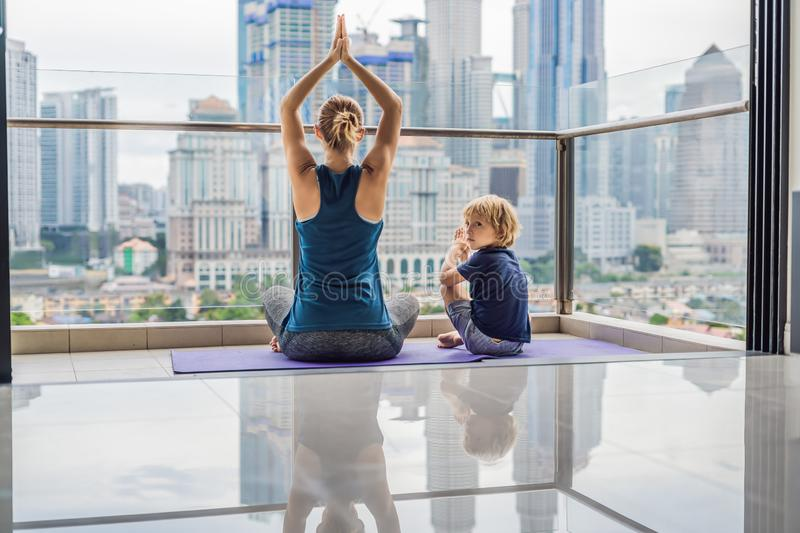 Mom and son are practicing yoga on the balcony in the background of a big city. Sports mom with kid doing morning work. Out at home. Mum and child do the stock photography