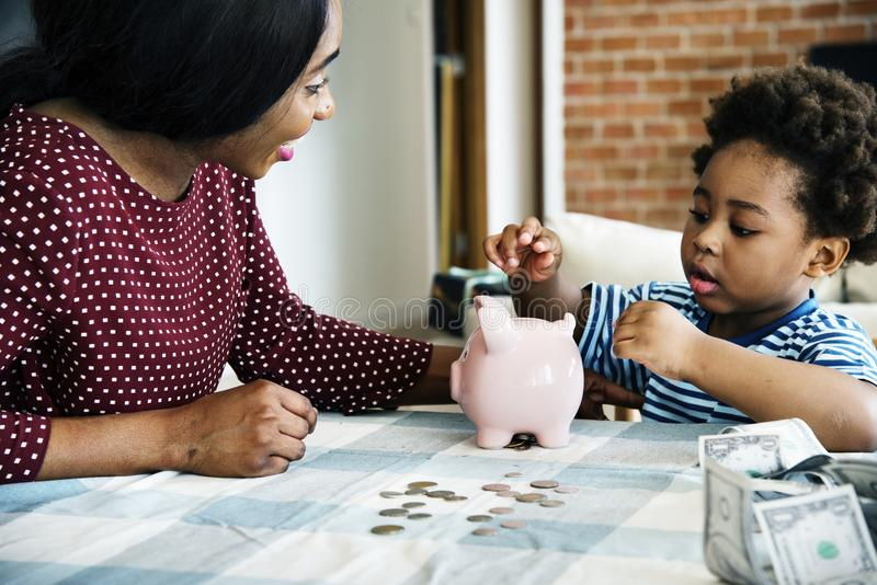 Mom and son saving money to piggy bank stock images