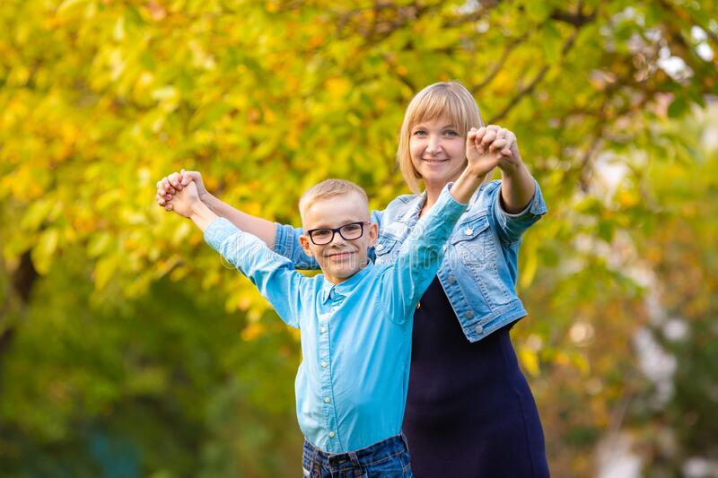 Mom and son seven-year-old son having fun in autumn park royalty free stock photos