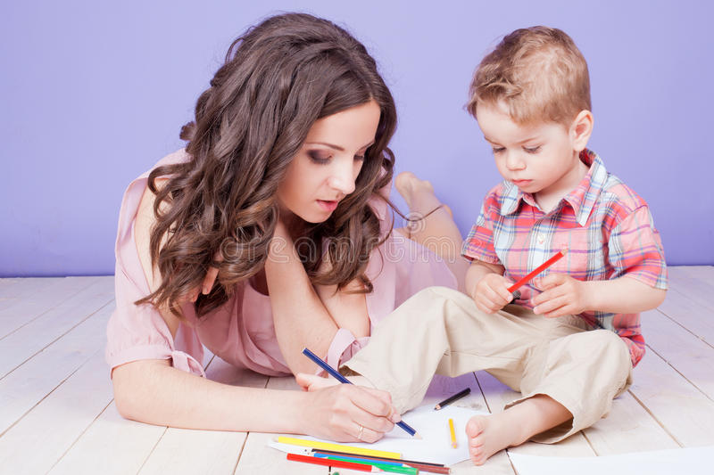 Mom son sit on the floor and paint. Mom and son sit on the floor and paint crayons royalty free stock photo