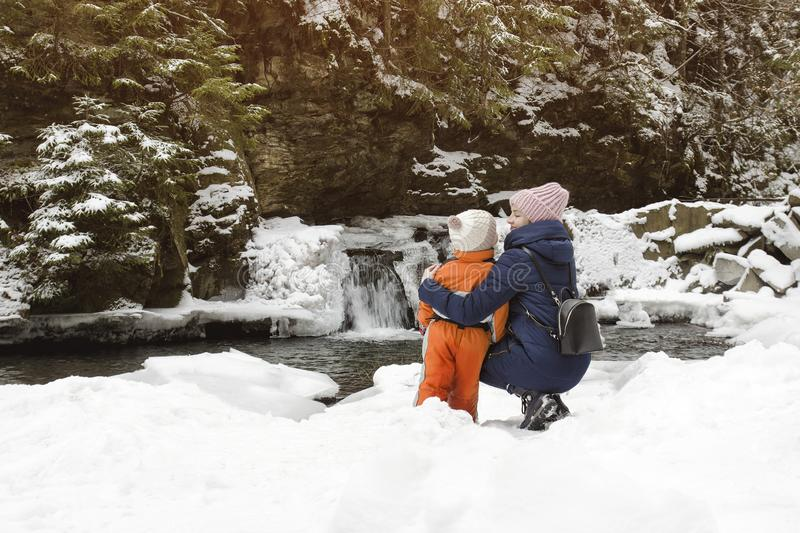 Mom and son sitting in embrace on a background of snow-covered waterfall, hill and pine forests. Winter cloudy day.  royalty free stock image