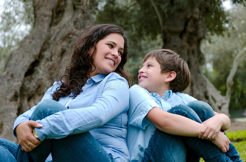 Mom and son sitting on green grass in green park. Concept of happy family relations stock images