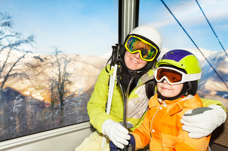 Mom and son skiers sit in cable car ski lift. Close portrait of mother and little boy son skier sit in cable car cabin on ski resort stock images