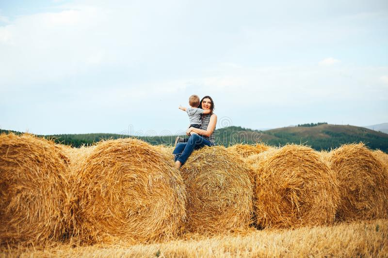 Happy mother with son in summer at field and straw haystack stock images