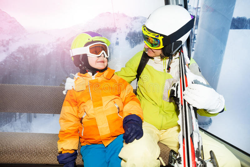 Mom and son talk in cable car cabin. Mother and child with ski helmet and mask sitting in cable car cabin lift in ski resort stock photos