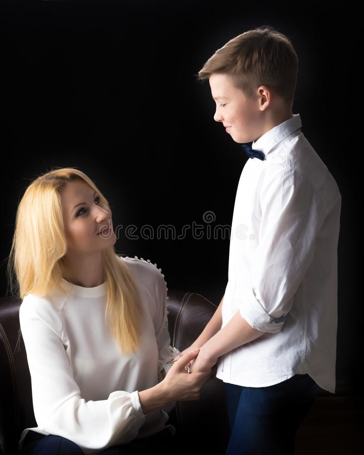 Mom and son teenager on a black background. The concept of happy childhood, People, harmonious development of the child in the family royalty free stock photography