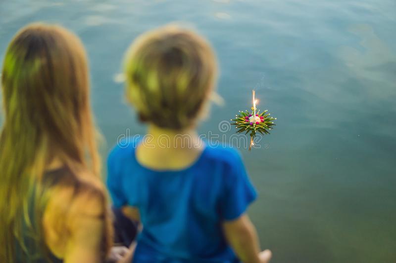 Mom and son tourists holds the Loy Krathong in her hands and is about to launch it into the water. Loy Krathong festival. People buy flowers and candle to royalty free stock images