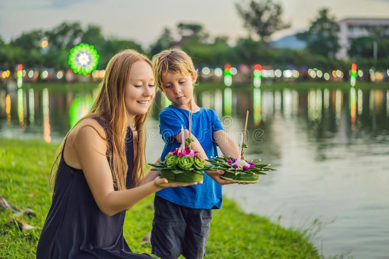 Mom and son tourists holds the Loy Krathong in her hands and is about to launch it into the water. Loy Krathong festival. People buy flowers and candle to stock photography
