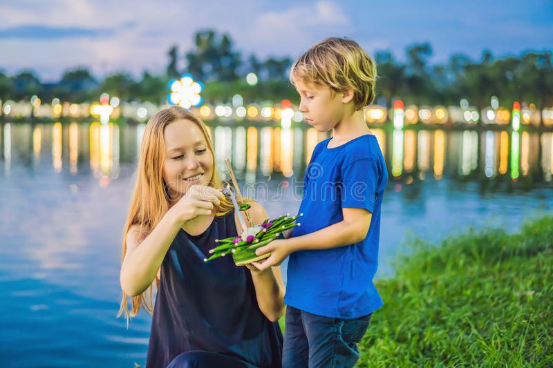 Mom and son tourists holds the Loy Krathong in her hands and is about to launch it into the water. Loy Krathong festival. People buy flowers and candle to royalty free stock image