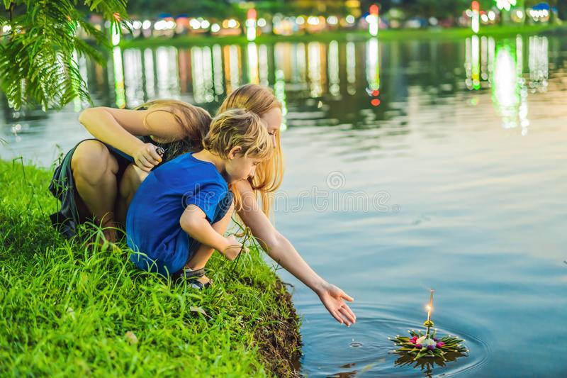 Mom and son tourists holds the Loy Krathong in her hands and is about to launch it into the water. Loy Krathong festival. People buy flowers and candle to stock photos