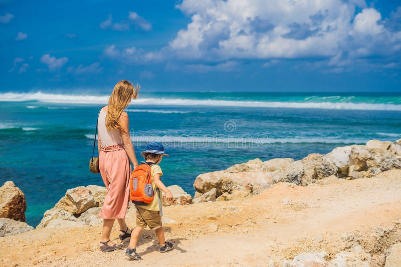 Mom and son travelers on amazing Melasti Beach with turquoise water, Bali Island Indonesia. Traveling with kids concept.  stock photos