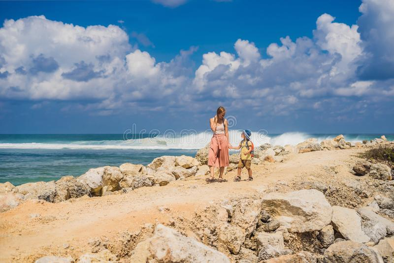 Mom and son travelers on amazing Melasti Beach with turquoise water, Bali Island Indonesia. Traveling with kids concept.  royalty free stock image