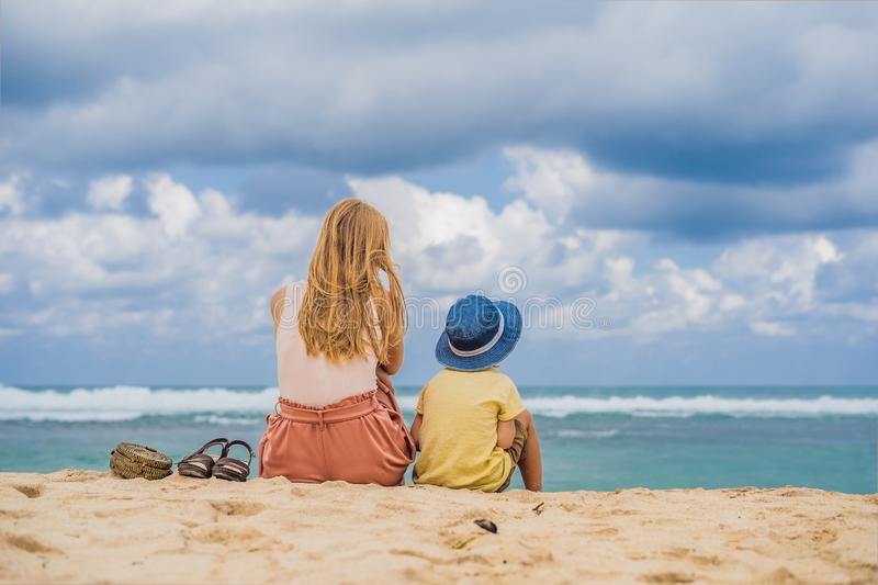 Mom and son travelers on amazing Melasti Beach with turquoise water, Bali Island Indonesia. Traveling with kids concept.  royalty free stock photos