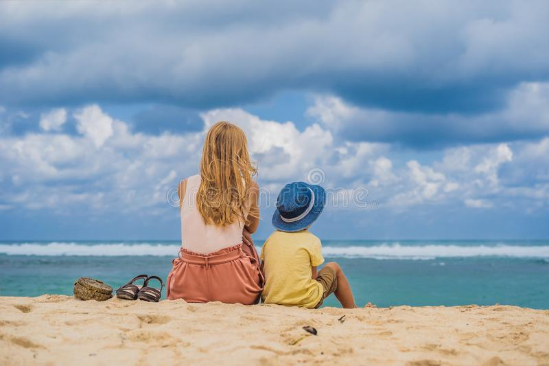 Mom and son travelers on amazing Melasti Beach with turquoise water, Bali Island Indonesia. Traveling with kids concept.  stock photography