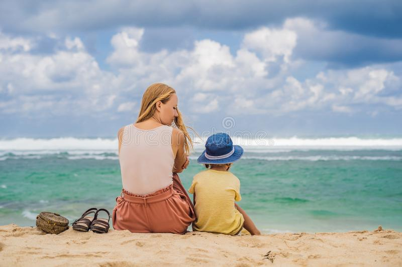 Mom and son travelers on amazing Melasti Beach with turquoise water, Bali Island Indonesia. Traveling with kids concept.  stock images