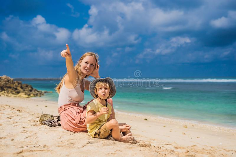 Mom and son travelers on amazing Melasti Beach with turquoise water, Bali Island Indonesia. Traveling with kids concept.  royalty free stock photography