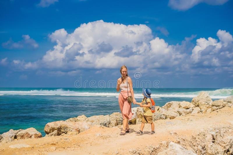 Mom and son travelers on amazing Melasti Beach with turquoise water, Bali Island Indonesia. Traveling with kids concept.  royalty free stock photo
