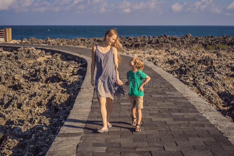 Mom and son travelers on amazing Nusadua, Waterbloom Fountain, Bali Island Indonesia. Traveling with kids concept.  royalty free stock image