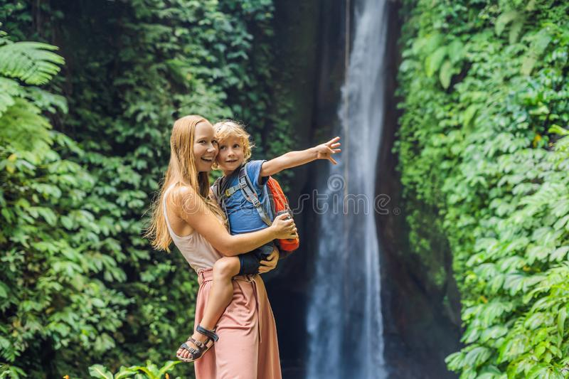 Mom and son travelers on the background of Leke Leke waterfall in Bali island Indonesia. Traveling with children concept.  royalty free stock image