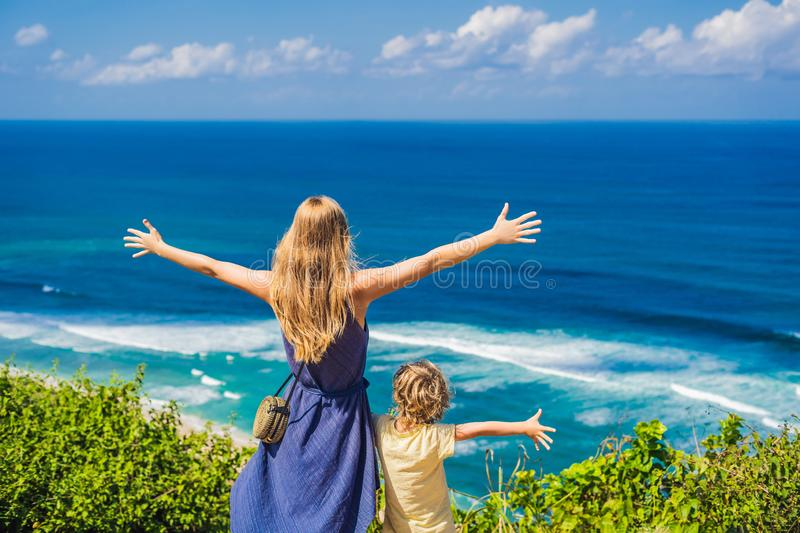 Mom and son travelers on a cliff above the beach. Empty paradise. Beach, blue sea waves in Bali island, Indonesia. Suluban and Nyang Nyang place. Traveling with royalty free stock photo