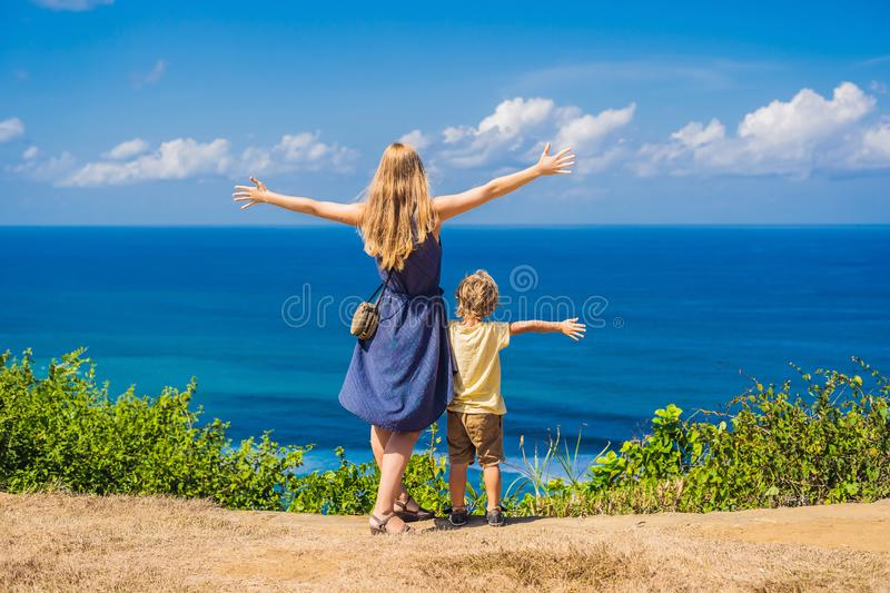 Mom and son travelers on a cliff above the beach. Empty paradise. Beach, blue sea waves in Bali island, Indonesia. Suluban and Nyang Nyang place. Traveling with stock photo