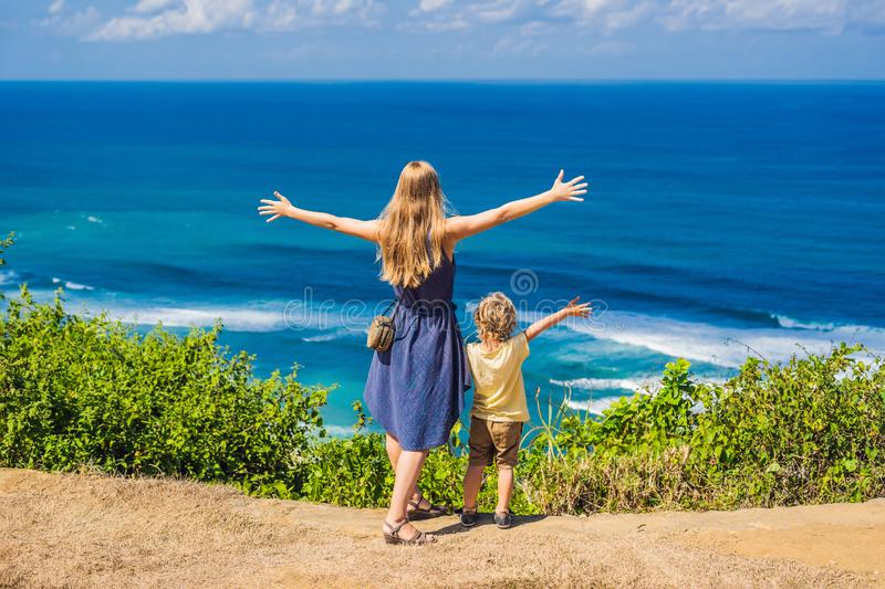 Mom and son travelers on a cliff above the beach. Empty paradise. Beach, blue sea waves in Bali island, Indonesia. Suluban and Nyang Nyang place. Traveling with stock photography