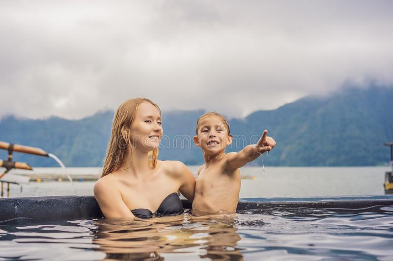 Mom and son travelers in Hot Springs in Bali on the background of lake. Traveling with children concept.  royalty free stock photos