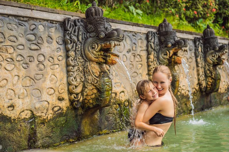 Mom and son travelers in hot springs banjar. Thermal water is released from the mouth of statues at a hot springs in. Banjar, Bali, Indonesia. Traveling with stock images