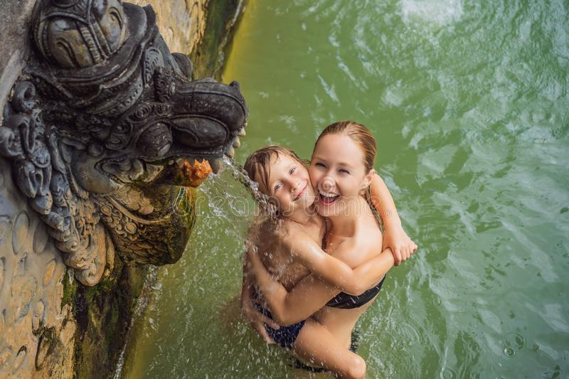 Mom and son travelers in hot springs banjar. Thermal water is released from the mouth of statues at a hot springs in. Banjar, Bali, Indonesia. Traveling with royalty free stock photography
