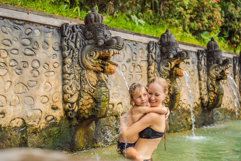Mom and son travelers in hot springs banjar. Thermal water is released from the mouth of statues at a hot springs in. Banjar, Bali, Indonesia. Traveling with royalty free stock photos