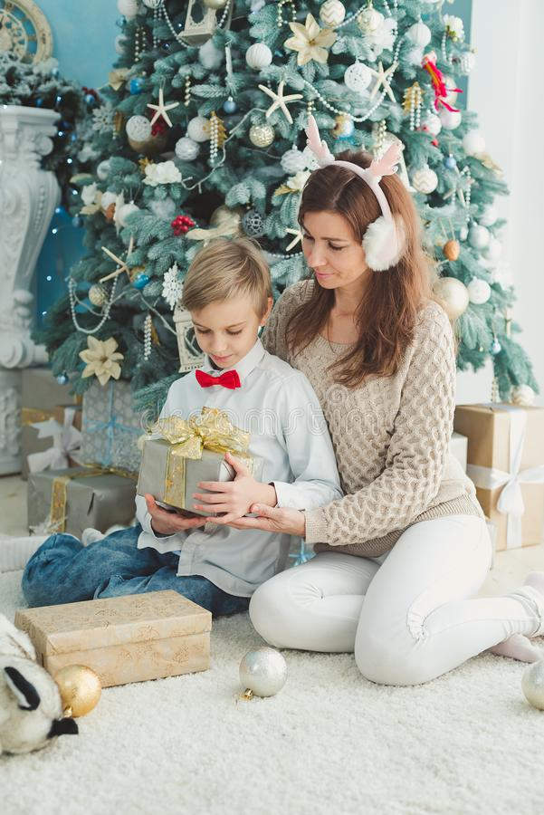 Mom and son under Christmas tree. Family holiday royalty free stock image