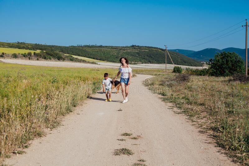 Mom and son walk with dog in yellow field stock photo
