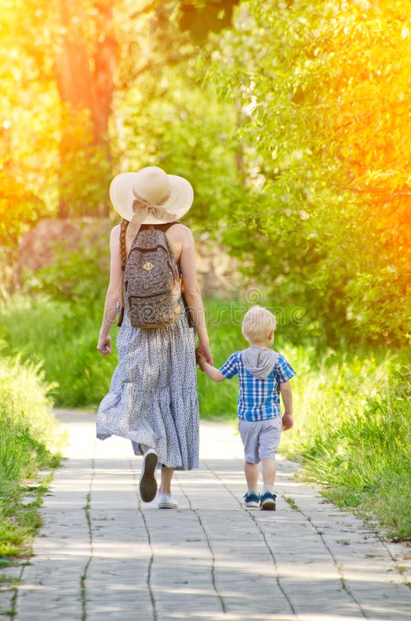 Mom and son walking along the road in the park. Back view stock photos