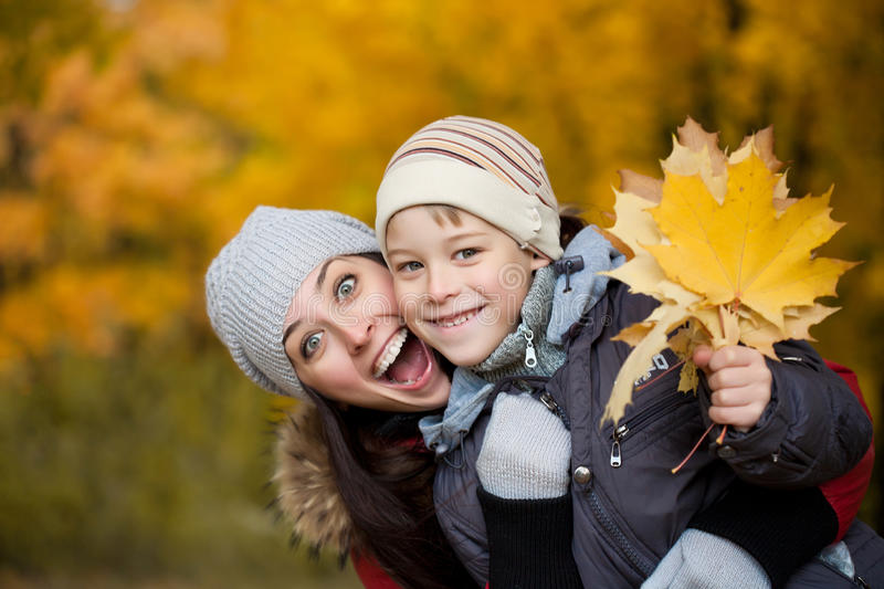 Mom and son on a yellow autumn park background stock photo