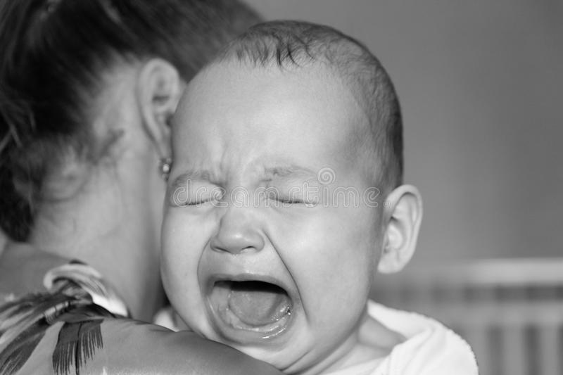 Mom soothes baby. The baby is crying royalty free stock image