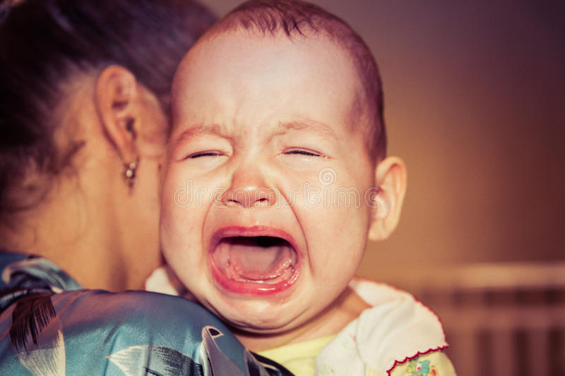 Mom soothes baby. The baby is crying stock images