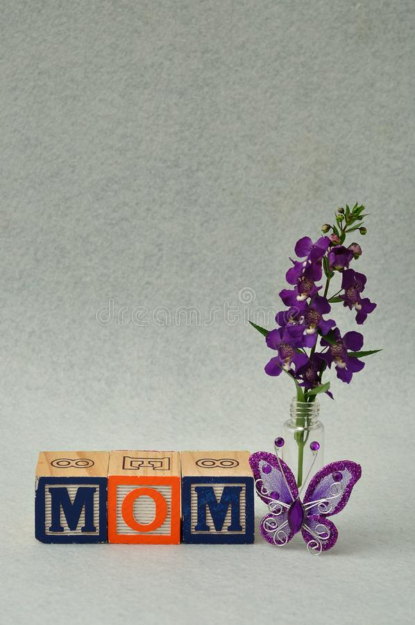 Mom spelled with alphabet blocks and small purple flowers royalty free stock image