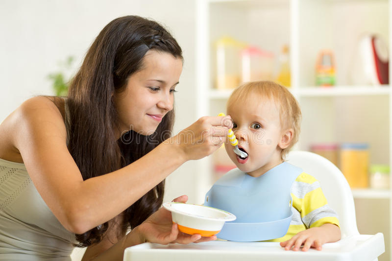 Mom spoon feeds child royalty free stock photo