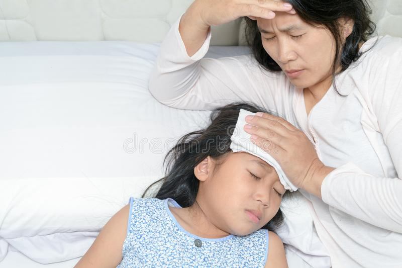 Mom suffering from migraine because her daughter sick stock photo